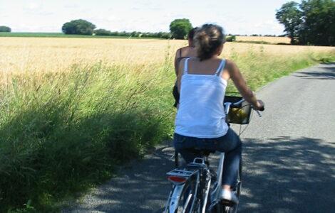 Deux filles font du vélo sur une route de campagne à coté d'un champ de blé